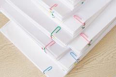 Pilha de papel e de relatórios da sobrecarga na tabela de madeira Foto de Stock