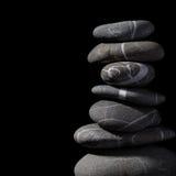 Pilha de pedras no fundo preto Fotos de Stock
