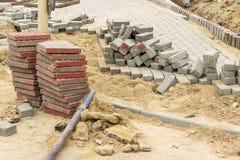 Pilha de pedras vermelhas do pavimento no local dos trabalhos de estrada Construção e reparo do passeio Melhoria de ruas da cidad fotos de stock royalty free