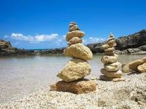 A pilha de Piramide de zen apedreja perto do mar e do céu azul Imagens de Stock