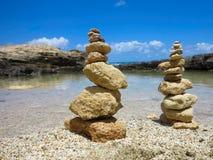 A pilha de Piramide de zen apedreja perto do mar e do céu azul Foto de Stock