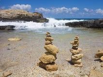 A pilha de Piramide de zen apedreja perto do mar e do céu azul Fotos de Stock Royalty Free