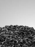Pilha de pneumáticos de borracha usados no fundo cinzento Fotografia de Stock
