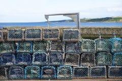 Pilha de potenciômetros da rede da lagosta no porto pela parede de pedra para que o pescador trave peixes e alimento de mar foto de stock