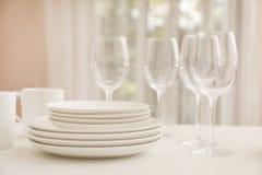 Pilha de pratos, de vidros e de copos limpos na tabela foto de stock royalty free