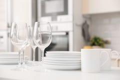 Pilha de pratos, de vidros e de copos limpos na tabela imagens de stock