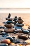 Pilha de rochas equilibradas na praia no tempo do por do sol Imagens de Stock