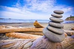Pilha de rochas na madeira lançada costa Foto de Stock