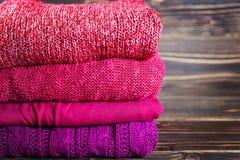 Pilha de roupa de confecção de malhas morna que encontra-se em uma tabela de madeira Imagem de Stock