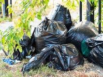 Pilha de sacos de lixo pretos com lixo fora imagens de stock