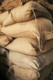 Pilha de sacos marrons de serapilheira com grão em um armazém Foto de Stock