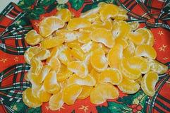 Pilha de seções da fatia da tangerina fresca no Natal b vermelho Fotografia de Stock Royalty Free