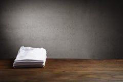 A pilha de seis dobrou as camisas brancas na tabela Fotografia de Stock