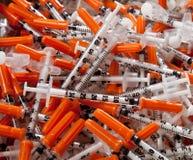 Pilha de seringas usadas com tampões alaranjados Fotografia de Stock Royalty Free