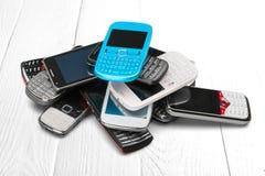 Pilha de smartphones velhos no fundo de madeira imagem de stock