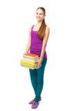 Pilha de sorriso feliz da terra arrendada da menina do estudante de livros Fotografia de Stock Royalty Free