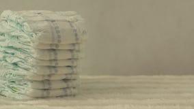 Pilha de tecidos do bebê em um fundo branco, espaço da cópia, close-up, conforto filme