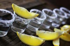 Pilha de tequila com sal e limão em um fundo de madeira Foto de Stock Royalty Free