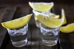 Pilha de tequila com sal e limão em um fundo de madeira Fotografia de Stock