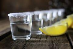 Pilha de tequila com sal e limão em um fundo de madeira Imagem de Stock