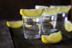 Pilha de tequila com sal e limão em um fundo de madeira Fotos de Stock Royalty Free