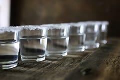 Pilha de tequila com sal e limão em um fundo de madeira Fotos de Stock