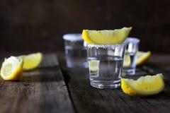 Pilha de tequila com sal e limão em um fundo de madeira Imagem de Stock Royalty Free