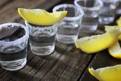 Pilha de tequila com sal e limão em um fundo de madeira Fotografia de Stock Royalty Free