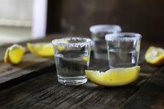 Pilha de tequila com sal e limão em um fundo de madeira Imagens de Stock