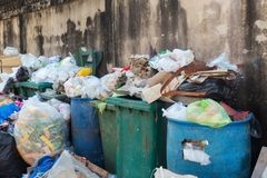 Pilha de tipos diferentes de grandes descarga de lixo, sacos de plástico, e escaninhos de lixo perto de uma parede na área urbana fotos de stock