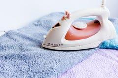 Pilha de toalhas coloridas com ferro no fundo da tela da lavanderia Foto de Stock
