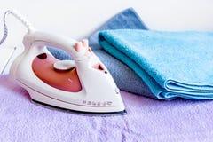 Pilha de toalhas coloridas com ferro no fundo da tela da lavanderia Imagem de Stock Royalty Free