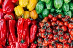 A pilha de tomates de cereja e de pimentas de sino arranjou agradavelmente no mercado do ` s do fazendeiro Fotos de Stock Royalty Free