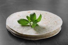Pilha de tortilhas saborosos com as folhas da manjericão na tabela cinzenta fotografia de stock