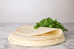 Pilha de tortilhas saborosos com folhas da manjericão Espa?o para o texto fotos de stock