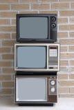 Pilha de três aparelhos de televisão Fotografia de Stock Royalty Free