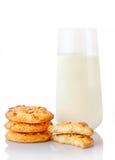 Pilha de três cookies de manteiga caseiros do amendoim, metades das cookies e vidro do leite Foto de Stock Royalty Free