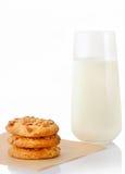 Pilha de três cookies de manteiga caseiros do amendoim no papel do cozimento e no vidro do leite Foto de Stock Royalty Free