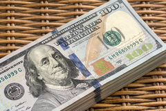 Pilha de USD 100 dólares de notas no fundo de vime Foto de Stock Royalty Free