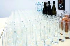 Pilha de vidros transparentes para o vinho, o suco, as garrafas do vinho e a água Foto de Stock Royalty Free
