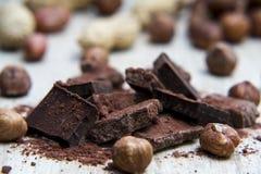 Pilha do chocolate com porcas e cascas de noz Imagens de Stock