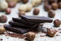 Pilha do chocolate escuro com porcas e cascas de noz Fotografia de Stock