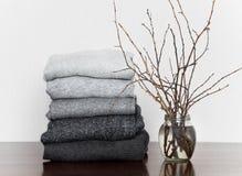 A pilha do cinza fez malha camisetas e um vaso com ramos na tabela de madeira, decorada com velas imagem de stock royalty free