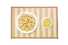 Pilha do close up do biscoito marrom no alfabeto inglês no prato branco e do chá marrom no copo cerâmico branco na esteira de mad fotos de stock