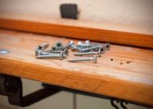 Pilha do close up do parafuso metálico no fundo de madeira fotografia de stock