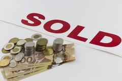 Pilha do dinheiro canadense com sinal vendido imagem de stock