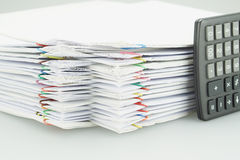 A pilha do documento branco da sobrecarga com calculadora preta colocou o vertical Imagem de Stock