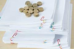 A pilha do documento tem a pilha do borrão de moedas de ouro Fotos de Stock