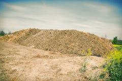 Pilha do estrume no campo com o céu nebuloso azul Montão do estrume no campo na jarda de exploração agrícola com a vila no fundo Foto de Stock