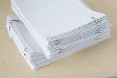 Pilha do papel e dos relatórios da sobrecarga com clipe de papel colorido Fotos de Stock Royalty Free